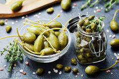Mixed capers in jar and bowl on black kitchen table. Mixed capers in jar and glass bowl on black kitchen table Royalty Free Stock Image