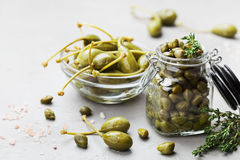Mixed capers in jar and bowl on white kitchen table. Royalty Free Stock Image