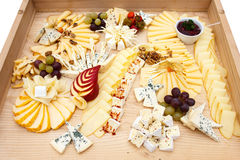 Mixed cheeses on a large light wooden board Stock Images