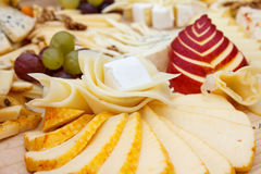 Mixed cheeses on light wooden board Royalty Free Stock Photos