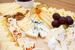 Mixed cheeses on light wooden board.  Stock Photos
