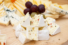 Mixed cheeses on light wooden board Stock Photography