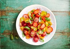 Mixed Cherry Tomato and Strawberry salad with honey-lemon dressing and basil royalty free stock photos