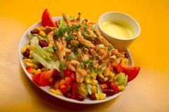 Mixed chicken salad. Mixed salad with chicken on a yellow table Royalty Free Stock Images