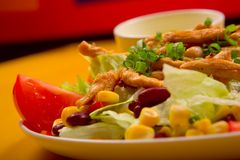 Mixed chicken salad. Mixed salad with chicken on the yellow table Stock Photo