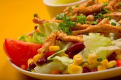 Mixed chicken salad. Mixed salad with chicken on the yellow table Royalty Free Stock Photography