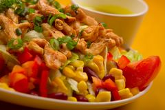 Mixed chicken salad. Mixed salad with chicken on the yellow table Royalty Free Stock Photo
