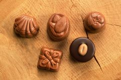 Mixed chocolate candies. On wood background royalty free stock images
