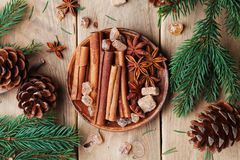 Mixed christmas spices in plate on wooden rustic table top view. Anise star, cinnamon sticks and brown sugar. Stock Images