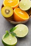 Mixed citrus fruit lemons, orange, kiwi, limes on a gray backgro Stock Photo