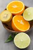 Mixed citrus fruit lemons, orange, kiwi, limes on a gray backgro Stock Photos
