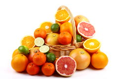 Mixed citrus fruit in wicker basket. Wicker basket with various types of citrus fruits on white background Royalty Free Stock Photo