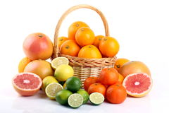 Mixed citrus fruit in wicker basket. Wicker basket with various types of citrus fruits on white background Royalty Free Stock Photography