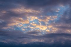 Mixed clouds dark evening skyscape. Mixed clouds and blue evening sky telephoto skyscape background Stock Image