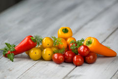 Mixed colored cherry tomatoes and mini paprika with fresh herbs on a wooden background Stock Photo