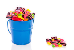 Mixed colorful candy sweets. In a blue bucket isolated over white Royalty Free Stock Images