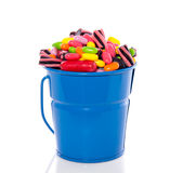 Mixed colorful candy sweets. In a blue bucket isolated over white Stock Images