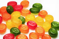Mixed colorful sweet baby candy lollipops lying on a white Stock Photos