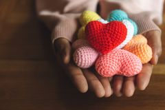 Mixed colors yarn heart on giving hands. Close up of colorful ha. Ndmade. Heart donation concept. Valentine love forever theme royalty free stock photography