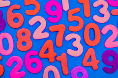 Mixed coloured numbers on a blue background. Stock Image