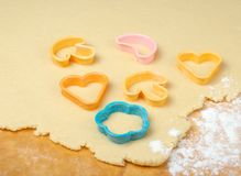 Mixed cookie cutters on wooden table. Stock Image