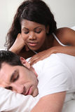 Mixed couple in bed. Girfriend watching her men sleep Royalty Free Stock Photos