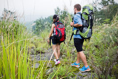 Mixed couple go trekking together, nature background Stock Images