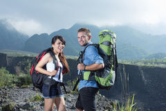 Mixed couple go trekking together, nature background Royalty Free Stock Images