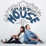 Mixed couple imaginating about smart house system, ilustrated th stock image