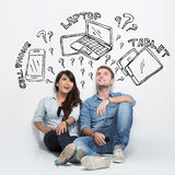 Mixed couple thinking about electronic between cellphone, laptop Royalty Free Stock Image