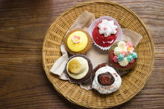 Mixed cupcakes. On wood table Royalty Free Stock Images