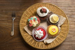 Mixed cupcakes. On wood table Royalty Free Stock Photos