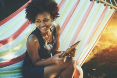 Mixed curly teenage female with digital tablet in hammock Stock Photos
