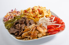 Mixed doner kebab on a plate. With french fries and salad Royalty Free Stock Photo