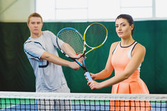 Mixed Doubles player hitting tennis ball, partner standing near net Royalty Free Stock Image