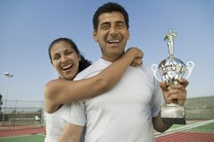 Mixed doubles Tennis Players standing in tennis court holding trophy portrait Stock Photography