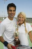 Mixed doubles Tennis Players on tennis court holding trophy portrait Royalty Free Stock Image