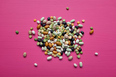 Mixed dried beans and peas on a pink background stock image