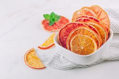 Mixed dried citrus orange and grapefruit slices in a white ceramic bowl. On light background. Selective focus stock images