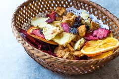 Mixed Dried Fruits Orange, Strawberry, Pineapple, Cherry and Apple Slices with Cinnamon Powder in Wooden Basket Royalty Free Stock Image