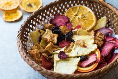 Mixed Dried Fruits Orange, Strawberry, Pineapple, Cherry and Apple Slices with Cinnamon Powder in Wooden Basket Royalty Free Stock Photography
