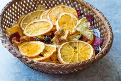 Mixed Dried Fruits Orange, Strawberry, Pineapple, Cherry and Apple Slices with Cinnamon Powder in Wooden Basket Stock Photo