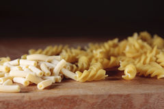 Mixed dried pasta. Dried macaroni and fusilli pasta on a wooden chopping board Royalty Free Stock Photos