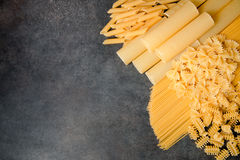 Mixed dried pasta selection on black wooden background Stock Image