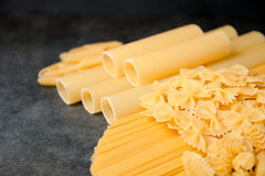 Mixed dried pasta selection on black wooden background Stock Images
