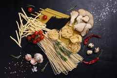 Mixed dried pasta selection with fresh ingredients: quail eggs, mushrooms, tomatoes, pepper, rosemary. Top view. Royalty Free Stock Photo