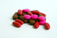 Mixed drugs. Mixed red, pink + brown drugs on white background Royalty Free Stock Photos