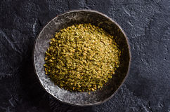 Mixed east spice - zaatar or zatar in metal vintage bowl on dark stone background. Selective focus Royalty Free Stock Image