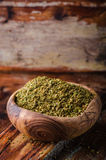 Mixed east spice - zaatar or zatar in vintage bowl on wooden background. Selective focus Stock Image