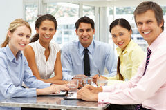 Mixed ethnic group in business meeting. Smiling to camera Stock Images